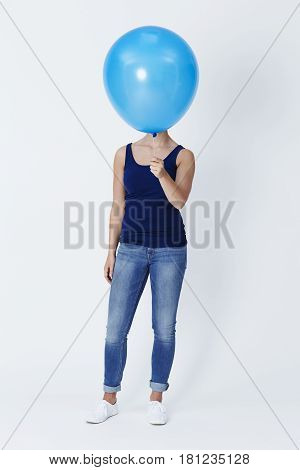 Blue balloon obscures model's face in studio