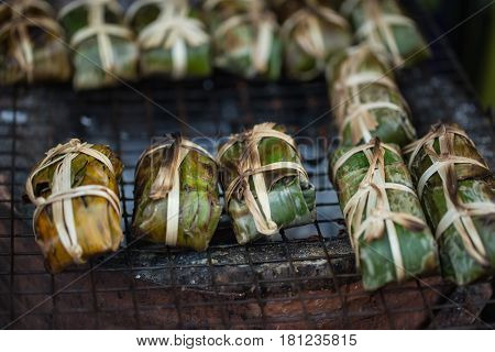 Thai style pork sour meat cover with banana leaf and grilled for food.