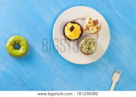 Cupcakes with buttercream. Glazed donut. Cake with pistachio nuts cream and small chocolate bar. Dessert with topping.