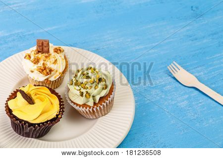 Cupcakes with buttercream. Sweet cake with pistachio nuts cream and small chocolate bar. Dessert with topping. On blue wooden rustic background.