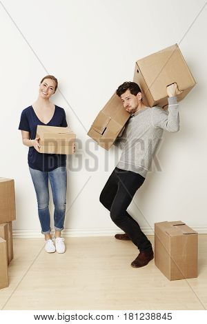 Young Couple moving home with man struggling