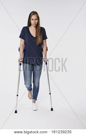 Woman with a sprain on crutches portrait
