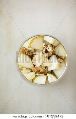 Oatmeal porridge flavoured with mashed banana topped with sliced pear walnuts almonds and honey view from above served in a clear round glass placed on a wooden light colored background