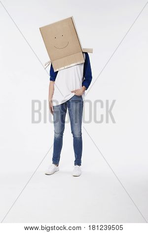Woman wearing cardboard box with smiley face