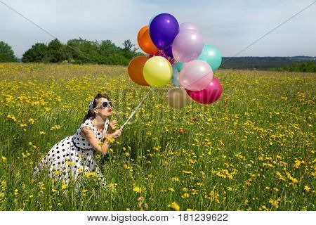 young pinup girl with a dotted petticoat dress and colorful balloons blowing on a blowball