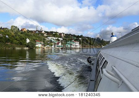 Motor boat and a small village on the Volga river in Russia