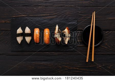 Sushi plate. Japanese food restaurant, unagi and salmon sushi on dark background. Set with chopsticks and soy sauce. Top view on black wood