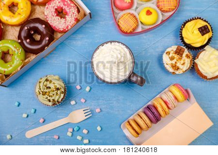 Donuts, cupcakes and macaroons. Mug with whipped cream. Cakes with buttercream. Almond macaron cookies. Sweet dessert.