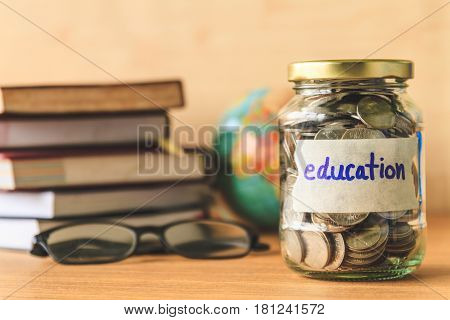 Coins in glass jar with education label booksglasses and globe on wooden table. Financial concept.