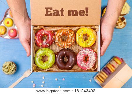 Donuts, cupcakes and macaroons. Male hands holding delivery box. Cakes with buttercream. Eat me text. Almond macaron cookies. Sweet dessert.