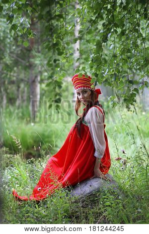 cute pretty girl in a traditional Slavic dress on nature in an unspoilt location