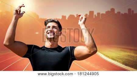 Digital composite of Male runner with hands in air on track against orange flare and blurry skyline