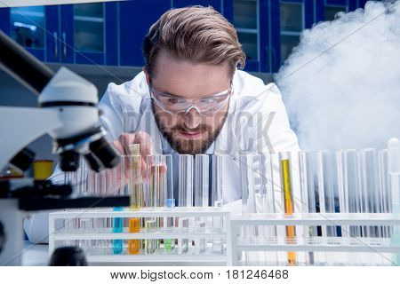 Bearded Chemist In Goggles With Reagents In Tubes And Microscope In Laboratory