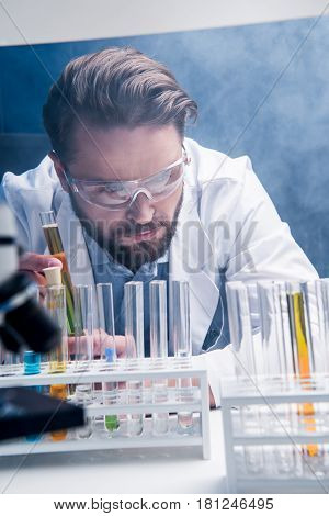 Concentrated Bearded Chemist In Goggles With Reagents In Tubes In Laboratory