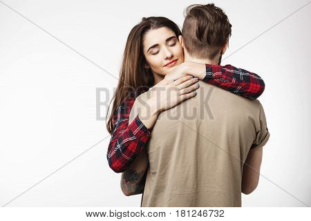 Tattooed man standing with back to camera, while beautiful girlfriend hugging him romantically. White background.