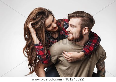 Young stylish woman sitting on man's back having fun, looking at him smilng cheefully.