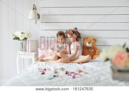 Pretty girl is laughing during watching something on her phone. The another girl is trying to realize what is going on. Kids are playing in white bedroom