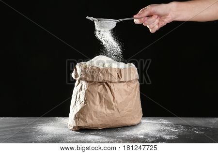 Bag of flour and female hand with sieve on dark background