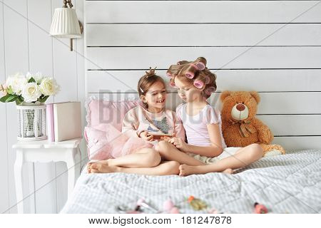 Two fancy girls are laying on a bed. One of them has found out something in her mobile phone which made her laugh amd she is showing it the another one