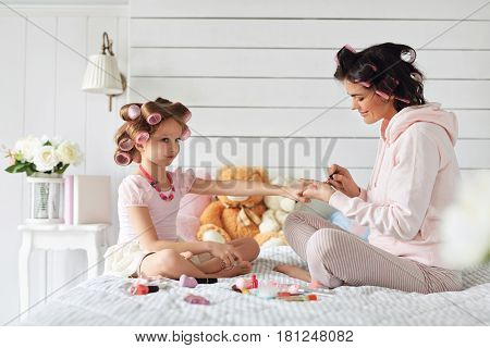 Mother and daughter are sitting on th bed. Woman is painting nails her daughter. They also have curlers on their heads.