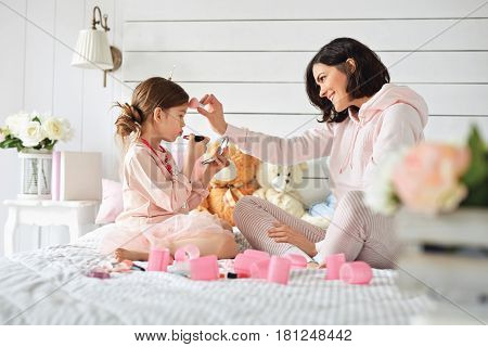 Young mother is teasing her daughter who is doing make up at the moment. They are dress up and sitting around girlish stuff