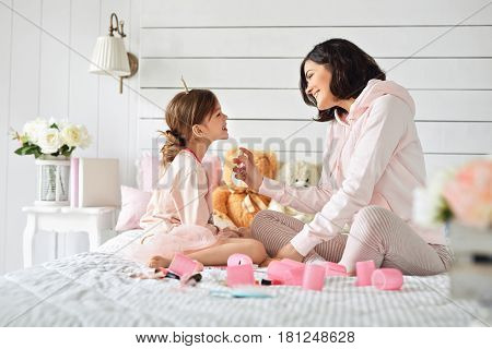 During the playing between mother and daughter, girl is starting to sprinkling perfume on her. Action is going on at the nice bedroom with toys, flowers and other girlish stuff