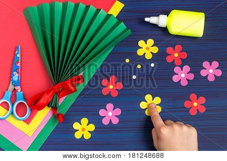 Making gift for Mother's Day by the child. Colorful bouquet of flowers out of paper. Children's art project. DIY concept. Step-by-step photo instruction. Step 5. Child glues middle of the flowers