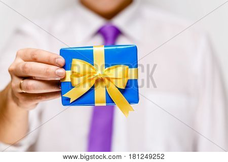 Male hand holding a gift box. Present wrapped with ribbon and bow. Christmas or birthday blue package. Man in white shirt and necktie.