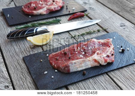 Raw beef steak on dark wooden table background. Fresh juicy meat on black stone cutting desk, knife and lemon slice. Cooking ingredients, butcher's and grocery concept