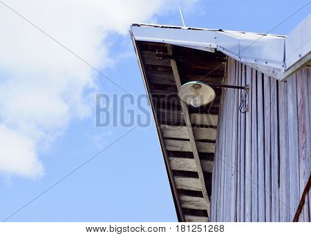 Old wooden farm barn peak with utility security light against blue and white fluffy clouds in sky