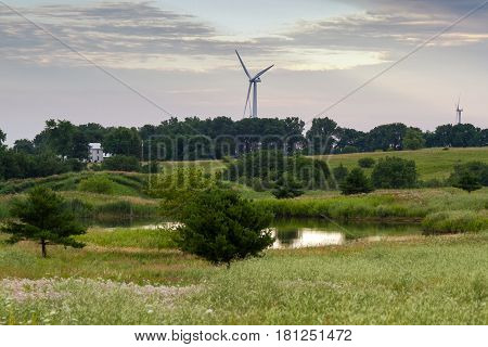 Farm scene with pond wind farm and pastures