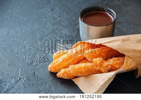 Churros Sprinkled With Sugar And Cinnamon Wrapped In Craft Paper And Hot Chocolate In Can Tin On A B