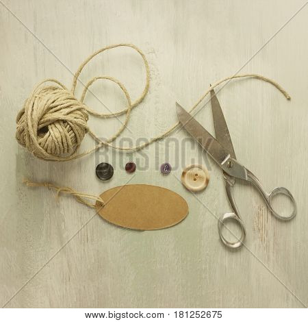 A square photo of vintage scissors with a roll of twine, a tag with copy space, and buttons, shot from above on light wooden boards background texture, toned image