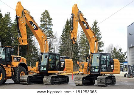 LIETO FINLAND - MARCH 25 2017: Cat 323FL and 316FL hydraulic excavators among Cat construction equipment seen at the annual public event of Konekaupan Villi Lansi Machinery Sales.
