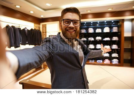 Selfie of bearded cute man wearing suit and glasses showing wardrobe and clothes