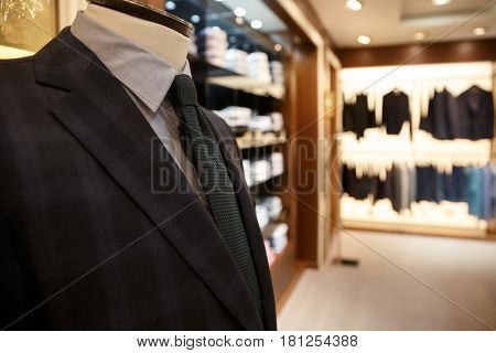 Close up shot of blue man jacket and grey shirt with tie on hanger in wardrobe