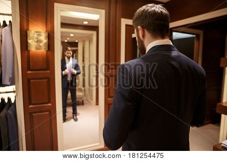Image of the back of man wearing blue costume standing near mirror in wood cloakroom