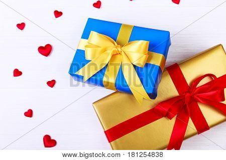 Gift boxes with red satin hearts. Presents wrapped with ribbon and bow. Christmas or birthday golden and blue paper package. On white table.