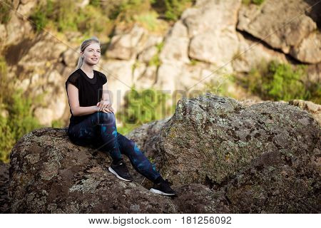 Young beautiful sportive girl smiling, sitting on rock in canyon. Copy space.