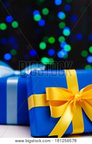 Gift boxes on blurred background. Presents wrapped with paper, bow and ribbons. Christmas or birthday packages. Celebration design.