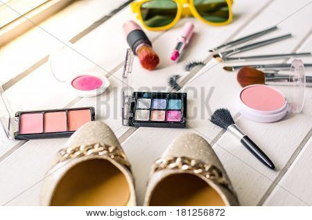 Cosmetics and apparel for women on the white wooden floor