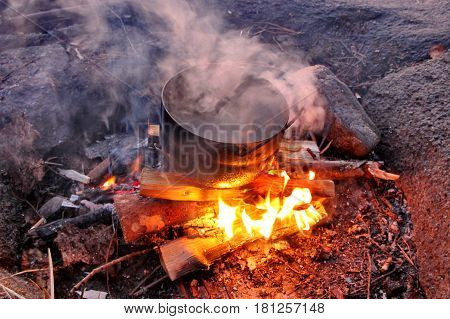 Close-up of a  metal  bowler of fish soup on the fire. Fishing, evening, fish soup, bonfire, fishing, summer.