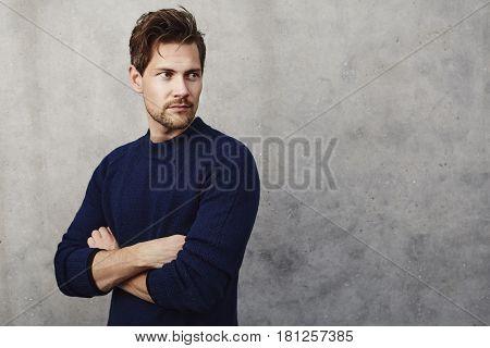 Dude in blue sweater looking away studio shot