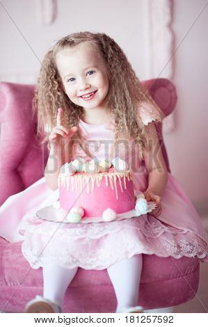 Smiling baby girl 4-5 year old holding birthday cake sitting in chair in room. Looking at camera. Celebration. Childhood.