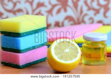 Bright cleaning sponge and rags set, olive oil in jar, lemon on a wooden table. Eco friendly house cleaning concept. Closeup