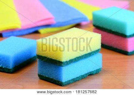 Colorful sponge and rags for cleaning ware and house cleaning. Cleaning sponge with scrub and rags set on a wooden table. Closeup
