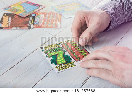 WROCLAW POLAND - MARCH 28th 2017: Man scratches Polish lottery scratchcard. Scratchcard is a small card where areas contain concealed information which can be revealed by scratching off an opaque covering.