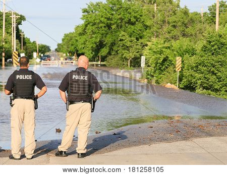 Policemen At A Flooded Street