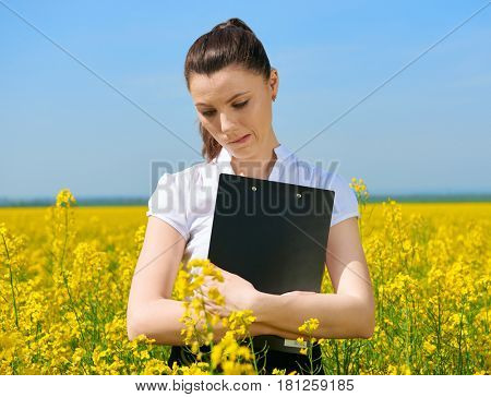 Sad business woman in flower field outdoor with clipboard. Young girl in yellow rapeseed field. Beautiful spring landscape, bright sunny day