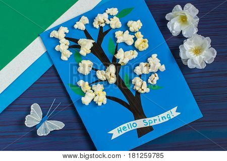 Making card by a child on spring theme. Blossoming tree on a blue background. Original children's art project. DIY concept. Step-by-step photo instruction. Step 8. Final result